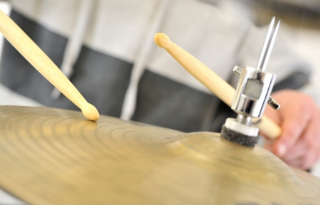 close up cymbal with drumsticks