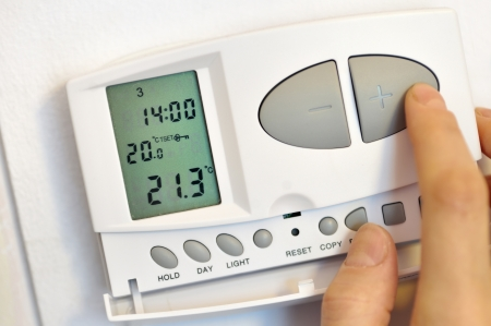 conditioning: hand pressing button on digital thermostat