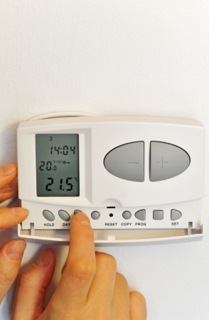 programmed: hand pressing button on digital thermostat  Stock Photo