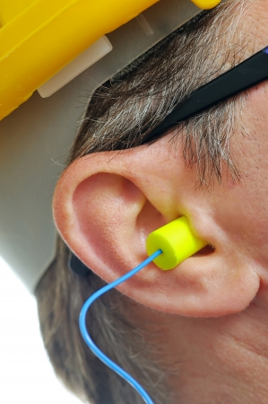 yellow earplug into the ear  Stock Photo
