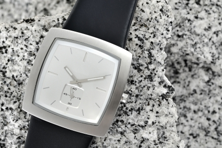 The arm watch with the leather strap on stone
