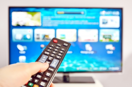 led screen: Smart tv and  hand pressing remote control Stock Photo