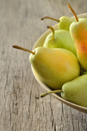 Fresh pears in bowl on wooden background Stock Photo - 18558614