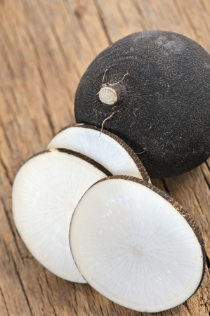 Black radish on a wooden board, whole and sliced