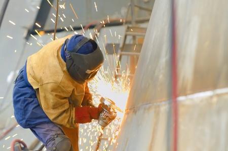 worker grinding metal inside of shipyard Stock Photo - 18841886