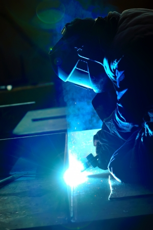 workplace safety: welder with protective mask welding metal and sparks