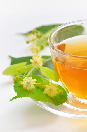 Glas kopje thee met linden op wit wordt geïsoleerd