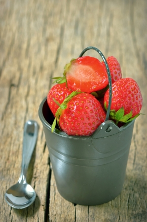 Fresh strawberries in bucket isolated on wooden background Stock Photo - 19986208