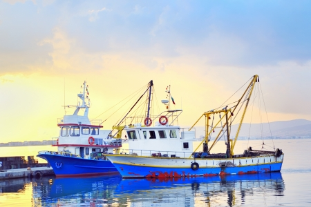 fishing boats under a sunset in a fishing harbor