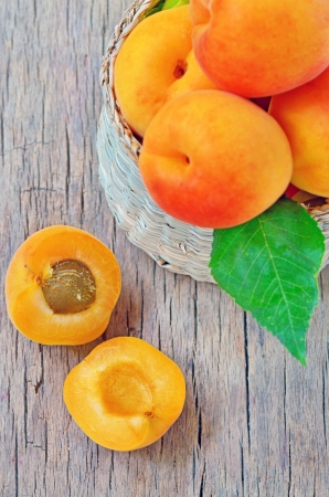 apricot fruits with green leaf and cut isolated on wooden background Stock Photo - 20764395