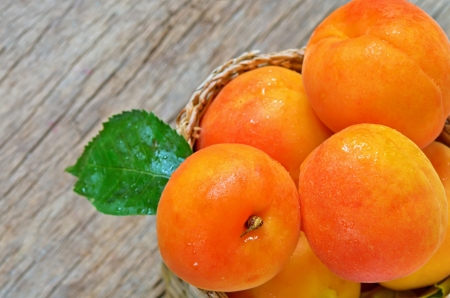 Apricots  on the old wooden table and basket shoot in studio Stock Photo - 20764396