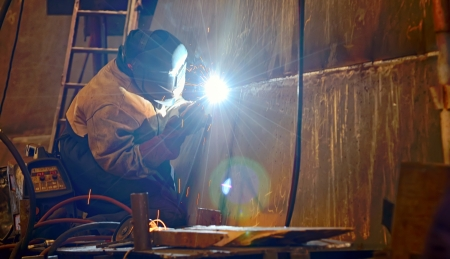 a welder working at shipyard building a ship photo