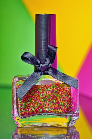 Bottle with colorful nail polish on colorful background Stock Photo - 21452203