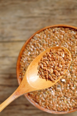 close up of flax seeds and wooden spoon on wood background; dietary supplement photo