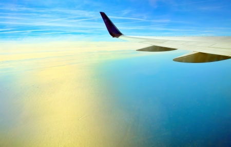 Wing of airplane flying over the ocean Stock Photo - 21452168