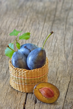 basket with plums on wooden background Stock Photo - 21451923