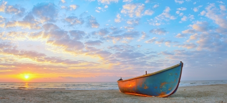 Fishing boat and sunrise on Black Sea beach photo