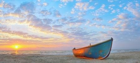 Vissersboot en zonsopgang op het strand Zwarte Zee