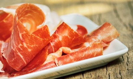Slices of prosciutto on old wood Stock Photo - 21885638