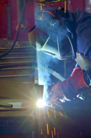 prefabricate: welder with protective mask welding metal and sparks