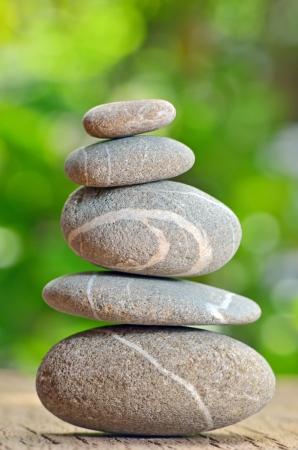 Gestapelde stenen op een groene natuurlijke achtergrond Stockfoto