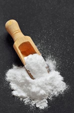bicarbonate: Wooden shovel with sodium bicarbonate on black