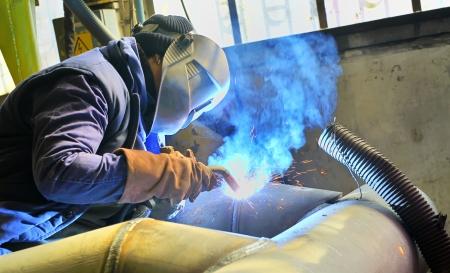 een lasser werken bij scheepswerf in dag tijd Stockfoto