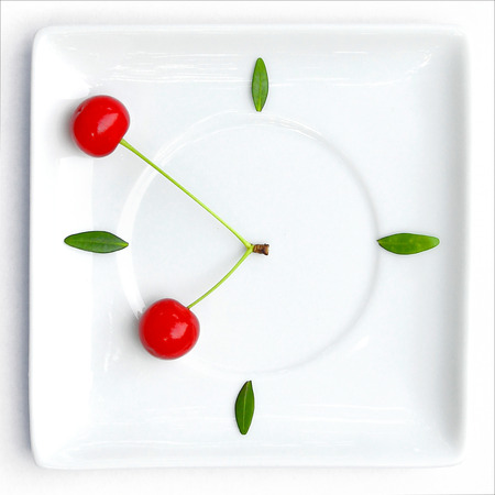 lunch time: cherry fruit clock isolated on plate, natural clock