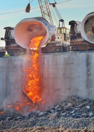 cast iron: hot steel pouring in steel plant. Production of cast iron in steel mills Stock Photo