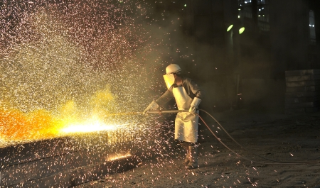 worker using torch cutter to cut through metal shoot in a plant photo