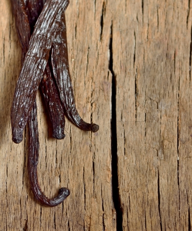 Bourbon vanilla beans isolated on old wooden background photo