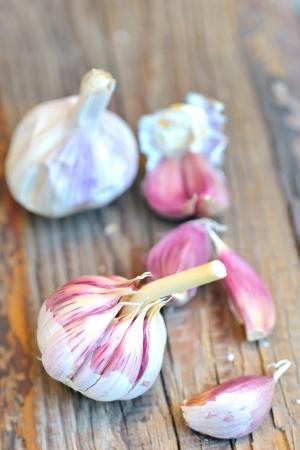 giardia: Garlic bulbs and cloves, over head view on pine wood table