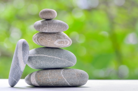Stacked stones on a green natural background