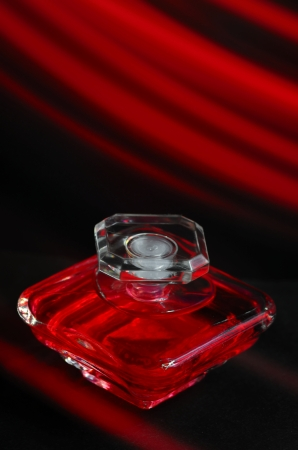 Bottle of red parfume on a red and black background, perfume bottle with glasses Stock Photo