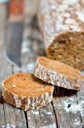Sliced loaf of rye bread on rustic wooden background