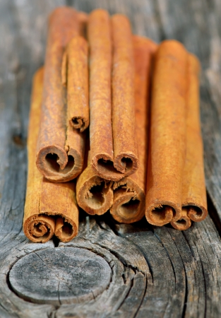 Cinnamon sticks in bucket on wooden background Stock Photo