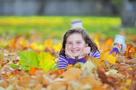 little girl laying on autumn leaves  Stock Photo