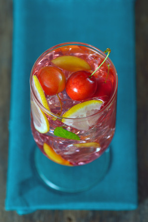 Cherry plum cocktail with ice, mint and lemon isolated. Above