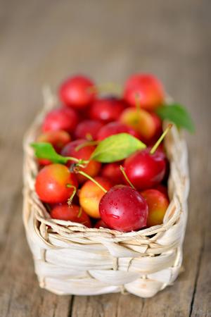 cherry-plum  in basket on wooden background
