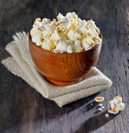 popcorn bowls: Fresh popcorn in bowl on old wooden table, isolated