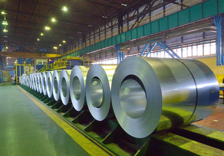 steel factory: packed coils of steel sheet inside of plant Editorial