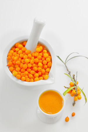 Sea buckthorn Berries and juice on white  Stock Photo