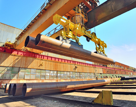 Loading pipes With Bridge Crane on industrial place photo
