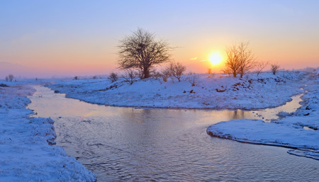 early spring snow: frozen sunset over winter river