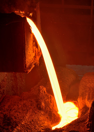 metal casting: Pouring of liquid metal in open hearth workshop of the metallurgical plant Stock Photo
