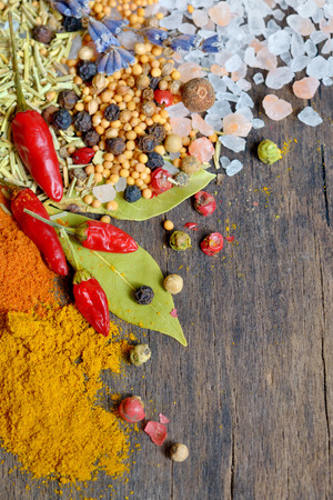 Colorful spices and herbs frame on a wooden . photo