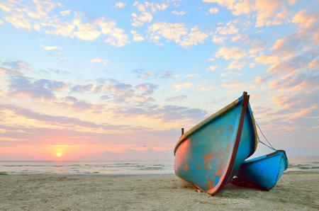 blue fishing boat at sunrise on black sea 版權商用圖片