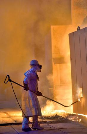 metallurgist: A steel worker takes a sample of hot steel