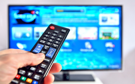 Smart tv and hand pressing remote control 스톡 콘텐츠