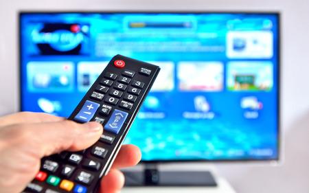 ver television: Smart TV y mano presionando control remoto Foto de archivo